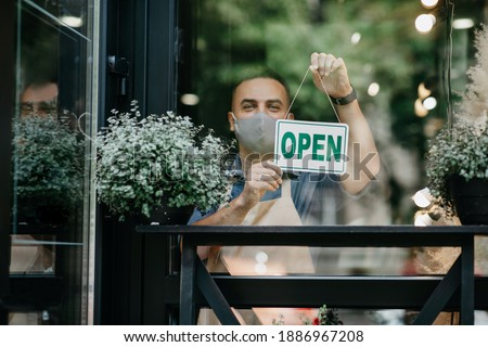Reopening of flower shop after covid-19 lockdown and new normal. Smiling young male owner in apron and protective mask turns sign with inscription is open on door, in studio with decorative plants