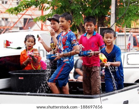 Chachoengsao Province 13 April 2014: Thai people and children wearing colorful clothes celebrate Songkran festival splashing water with bowls and water spray guns on the street in cities of Thailand  #188697656