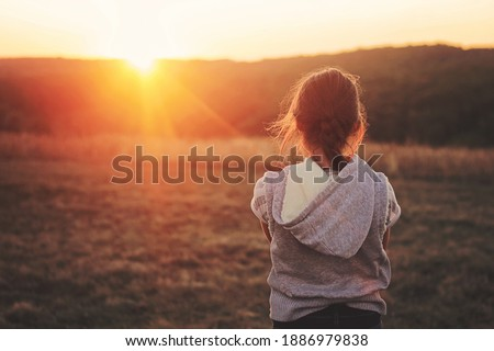 a girl watches a beautiful sunrise or sunset, she is in the rays of the sun #1886979838