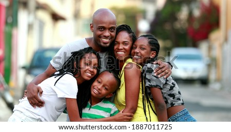 Happy African family portrait standing for photo outside. Cheerful black parents and children Royalty-Free Stock Photo #1887011725