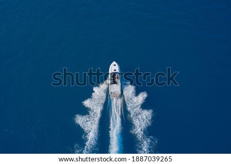 luxury motor boat. Aerial view of a boat in motion on blue water. Top view of a white boat sailing in the blue sea. Drone view of a boat sailing at high speed. Royalty-Free Stock Photo #1887039265