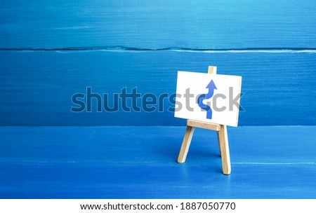 An easel with a curved arrow avoiding an obstacle. Deviation from route, side mission. Maneuvering, taking right action. Purposefulness and perseverance, confident movement towards the assigned goal. Royalty-Free Stock Photo #1887050770