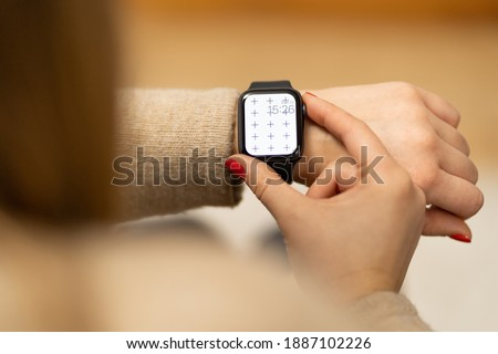 Smartwatch on girls hand with blank screen mock-up for your design at home office sitting on the couch near green plant with blurry background with free space for custom text