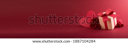 Paper art Valentine's day concept banner with hand made gift box, paper cut ribbon, bow, and a lot of hearts on a red background with space for text. Royalty-Free Stock Photo #1887104284
