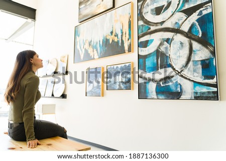 Side view of a beautiful young woman studying and watching the abstract paintings and colorful canvases during a visit to the art gallery  Royalty-Free Stock Photo #1887136300
