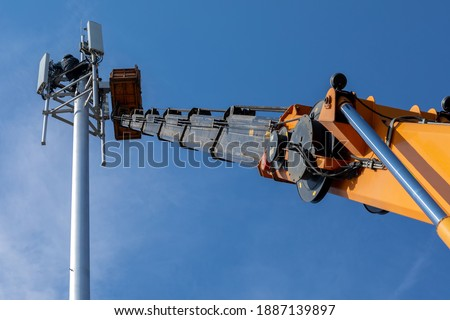 Crane with telescopic boom lift used as an aerial working platform. Worker install cellular base station with transmitters 3G, 4G and antennas on cell tower on background of blue sky. Focus on arrow. #1887139897