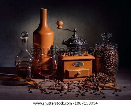 Coffee still life. Coffee beans are scattered on a wooden table near a coffee grinder and a glass jar. There is a snifter with cognac and a ceramic bottle nearby. Lays cinnamon sticks, anise, and nutm Royalty-Free Stock Photo #1887153034