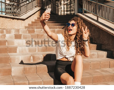 Beautiful smiling model with afro curls hairstyle dressed in summer hipster clothes.Sexy carefree female sitting on  stairs in the street in sunglasses.Taking selfie self portrait photos on smartphone