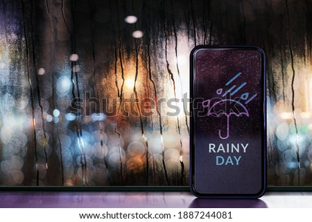 Rainy Day at Night in City Concept. Weather Forecast via Mobile Phone. Raindrops on Glass Window. Blurred Urban Lights as Outside View