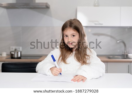 Cute little girl in headphones watching a video tutorial on drawing in an album, little preschooler draws pictures, child learns online at home, home learning concept