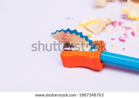 Blue pencil sharpening in orange pencil sharpener. School pencil sharpener. Office pencil sharpener