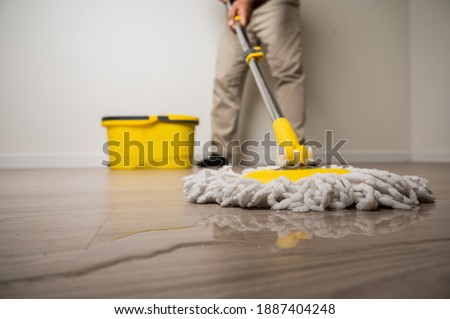 Cleaning workers mopping the wet area. There was spill water on the wooden floor in the living room. Royalty-Free Stock Photo #1887404248
