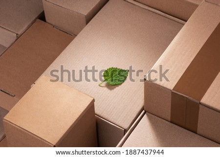 Fresh green leaf laying between cardboard boxes. Shipping deliveries, global trade and environmental impact. Royalty-Free Stock Photo #1887437944