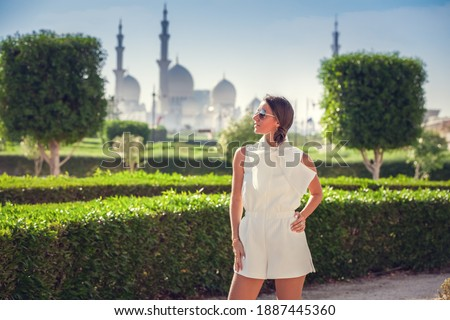 Young Woman standing near the Sheikh Zayed Grand Mosque, famous Abu Dhabi sightseeing. Traveling by Unated Arabic Emirates.  (soft focus) Royalty-Free Stock Photo #1887445360