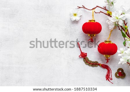 Flat lay of Chinese New Year decoration flowers and red lanterns Royalty-Free Stock Photo #1887510334