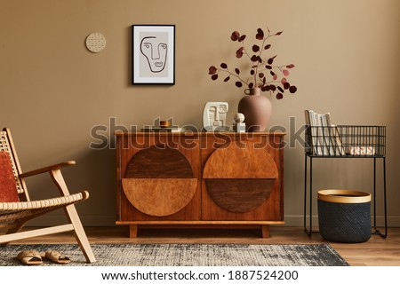 Interior design of unique living room with stylish commode, armchair, dired flowers in vase, mock up poster on the wall, carpet, decoration and personal accessories in modern home decor. Template. Royalty-Free Stock Photo #1887524200