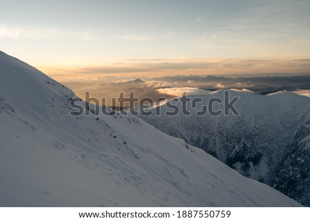 Blizzard in the mountains. Hikers returning happy on the ridge after reaching the summit in a strong foehn wind. Picture shows leisure outdoor activities.