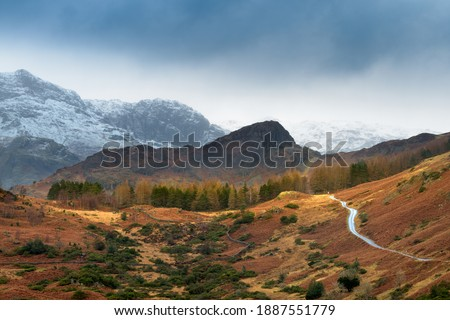Single track road leading through rural countryside with snowcapped mountains and dark Winter clouds. Langdale, Lake District, UK. Royalty-Free Stock Photo #1887551779