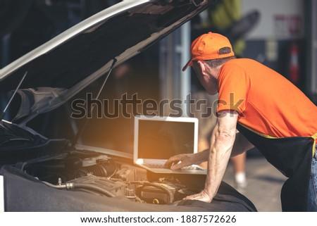Car maintenance service, technician diagnose car engine failure problem by laptop computer. Royalty-Free Stock Photo #1887572626