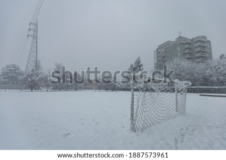 Milan, Italy - December 28, 2020: street view of Milan during the snow blizzard of late December, a soccer field is visible. Royalty-Free Stock Photo #1887573961