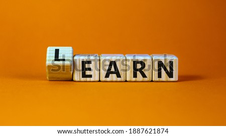 Learn or earn symbol. Turned a cube and changed the word 'earn' to 'learn'. Beautiful orange background. Business and learn or earn concept. Copy space.