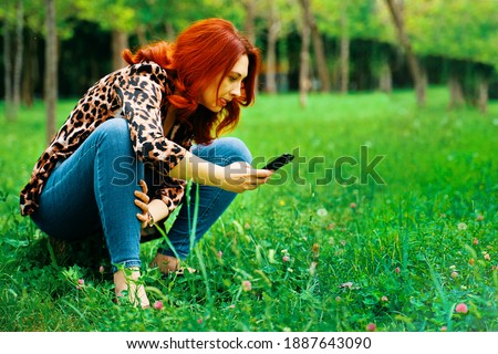 Person takes a picture of grass. Red-haired woman taking photos of nature in the Park. Trendy leopard print jacket and blue jeans. Walk in the summer park. Woman with a funny expression face.
