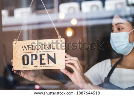 Young asian owner retail,coffee shop woman turning sign board to open with wearing face mask,protection to pandemic of coronavirus.Close, closed store,restaurant due to lockdown, quarantine of covid.