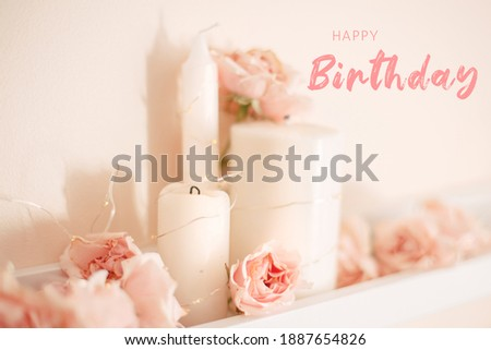 Happy Birthday card with greeting text. Decoration of  room for birthday celebration. Closeup of tender light pastel pink roses and white candles on shelf for themed party.