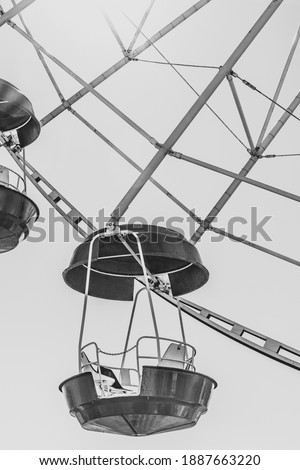 Ferris wheel booths in black and white image. The cabin of the Ferris wheel against the sky on top.Background image of the Ferris wheel. vertical image #1887663220