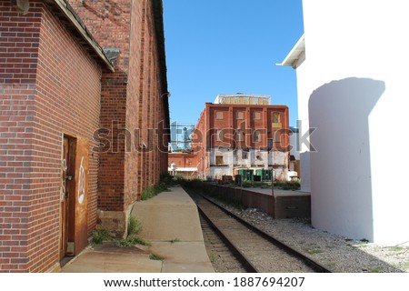 Old sugar beet factory abandoned.  Derelict building in Ault, CO.  Condemned factory in shambles.  Railway tracks leading to building. Royalty-Free Stock Photo #1887694207