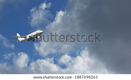 Zoom photo of passenger airplane taking off in deep blue  slightly cloudy sky as seen from the ground