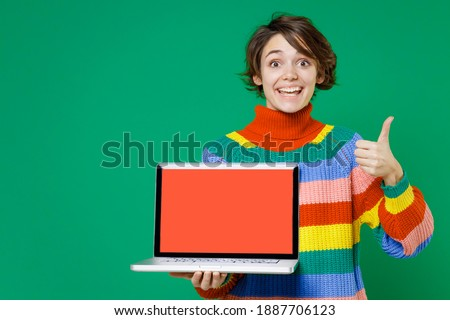 Excited funny young brunette woman 20s years old in casual colorful sweater hold laptop pc computer with blank empty screen showing thumb up isolated on bright green color background studio portrait