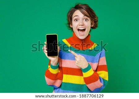 Excited young brunette woman 20s years old wearing casual colorful sweater pointing index finger on mobile cell phone with blank empty screen isolated on bright green color background studio portrait