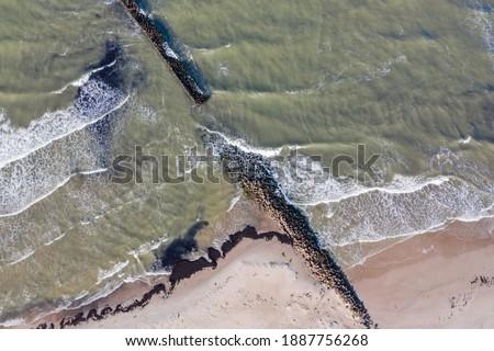 Aerial top down view of waves breaking against old stone breakwater pier in sea #1887756268