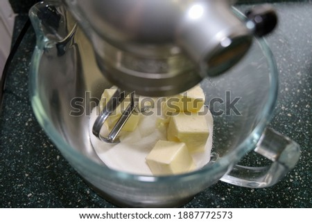 Sugar and butter in a glass mixer bowl to mix for sugar cookies.