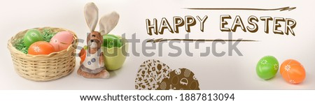 Colorful eggs in a basket. Decorative rabbit with green easter  egg. Happy Easter. Easter Congratulations Card. Easter decoration, banner, panorama, background.