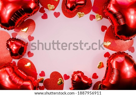 Text frame with red and gold hearts foil balloons top view on pink Valentine's Day background. Copyspace.