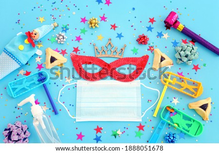 Purim celebration concept (jewish carnival holiday) over blue background. Top view, Flat lay. Coronavirus prevention concept, medical mask and sanitizer gel