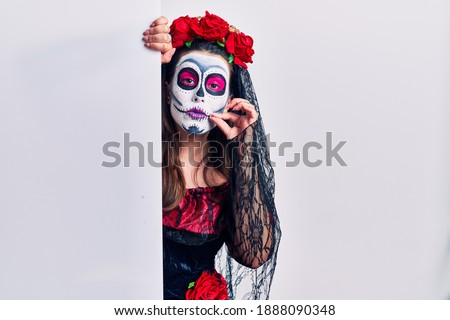 Young woman wearing day of the dead custome holding blank empty banner mouth and lips shut as zip with fingers. secret and silent, taboo talking