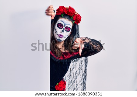 Young woman wearing day of the dead custome holding blank empty banner looking unhappy and angry showing rejection and negative with thumbs down gesture. bad expression.