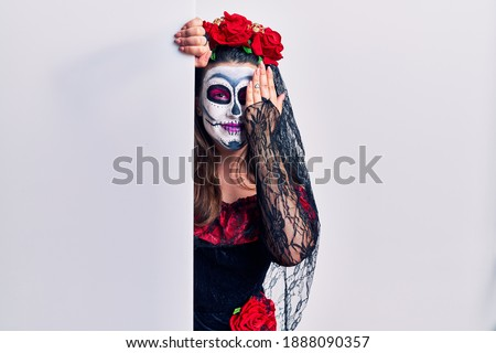 Young woman wearing day of the dead custome holding blank empty banner covering one eye with hand, confident smile on face and surprise emotion.
