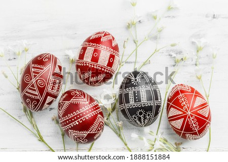 Red and black handmade Easter Pysanka eggs. Ukrainian pysanky decorated with wax-resist dyeing technique. White wooden background Royalty-Free Stock Photo #1888151884