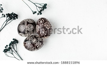 Black handmade Easter eggs. Ukrainian pysanka decorated with wax-resist dyeing technique. White background with copy empty space for text Royalty-Free Stock Photo #1888151896