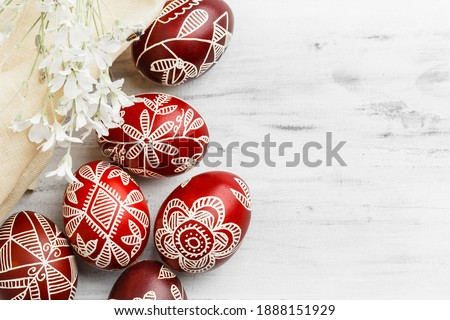 Red and white handmade Easter eggs. Ukrainian pysanka decorated with wax-resist dyeing technique. White wooden background with copy space for text Royalty-Free Stock Photo #1888151929