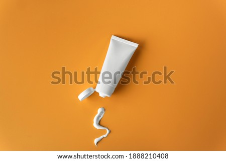 Top view blank label facial skincare white tube bottle with lid open product squeezed lotion or cream texture on plain solid orange background Royalty-Free Stock Photo #1888210408