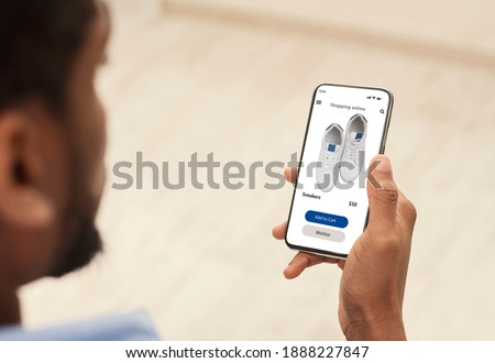 Application Or Website For Online Store. Over the shoulder view of black man using smartphone, browsing internet shop with shoes, choosing new sneakers footwear. Ecommerce, Retail, Sale And Discount Royalty-Free Stock Photo #1888227847