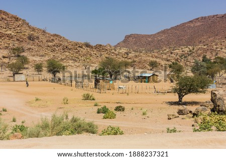 rural landscape scene in Namibia of clay huts and a small human settlement in the harsh arid environment  Royalty-Free Stock Photo #1888237321