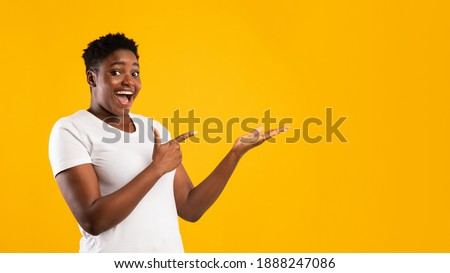 Excited Plus-Size Black Woman Showing Invisible Object Pointing Fingers Aside Advertising Your Text Posing Standing On Yellow Studio Background, Smiling To Camera. Blank Space, Panorama Royalty-Free Stock Photo #1888247086