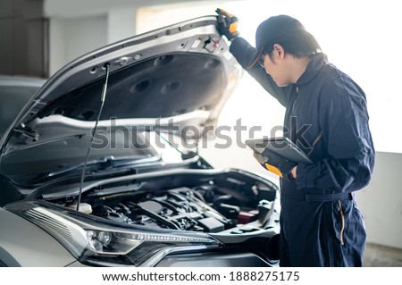 Asian auto mechanic holding digital tablet checking car engine under bonnet hood in auto service garage. Mechanical maintenance engineer working in automotive industry. Automobile servicing and repair Royalty-Free Stock Photo #1888275175