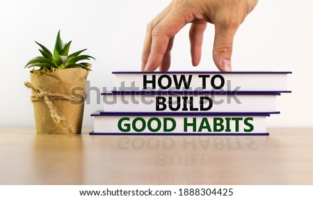 Build good habits symbol. Books with text 'how to build good habits' on beautiful wooden table. Male hand, house plant. White background. Business and build good habits concept. Copy space. Royalty-Free Stock Photo #1888304425